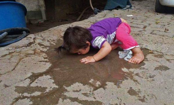 A child drinks from a puddle during the state of emergency in Cizre and other Turkish cities. Photo: IPPNW Germany